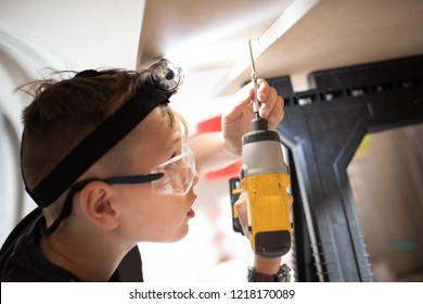 A handsome little boy with ADHD, Autism, Aspergers Syndrome, using a drill with a head torch and safety eye glasses on for protection, DIY homework project for school