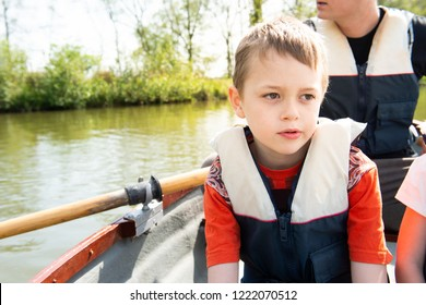 A handsome little boy with ADHD, Autism, Aspergers Syndrome wearing a life jacket enjoys a day on a rowing boat with is father in the summertime