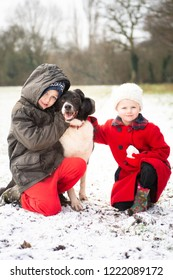 A handsome little boy with ADHD, Autism, Aspergers syndrome poses with his sister and loyal pet dog in the snow covered fields at Christmas, Xmas