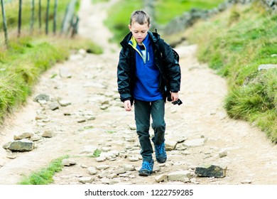 A handsome little boy with ADHD, Autism, Aspergers Syndrome paddles and wades through a cold river but slow flowing river in the Derbyshire Peak District National Park