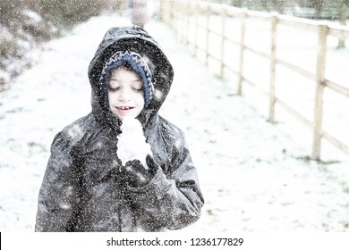A handsome little boy with ADHD, Autism, Aspergers Syndrome wrapped up warm and playing outside in the snow at Christmas time, Christmas Eve, Xmas