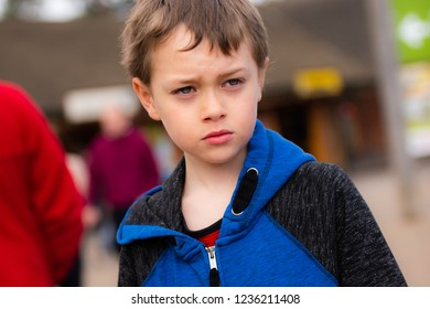A handsome little boy with ADHD, Autism, Aspergers Syndrome looking nervously into the distance, worried, scared