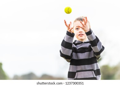 A handsome little boy with ADHD, Autism, Aspergers Syndrome practices his catching coordination with a tennis ball at the park, tennis coaching