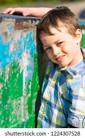 A handsome little boy with Autism, ADHD, Aspergers Syndrome poses for a picture wearing a chequered shirt, relaxed and calm