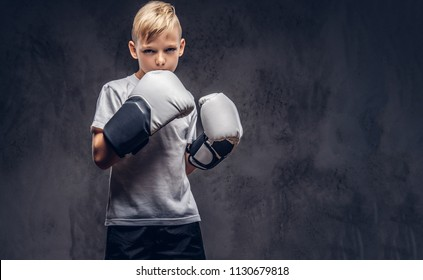 A handsome little boy boxer with blonde hair dressed in a white t-shirt in gloves ready to fight. Isolated on a dark textured background.