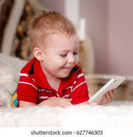 Handsome little boy with cell phone playing at home