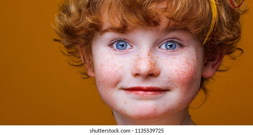 handsome little boy close-up portrait, kid face with freckles, baby with feathers on head