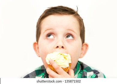 handsome little boy eating a fresh cream cup cake with messy face