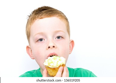 handsome little boy eating a fresh cream cup cake with messy fac