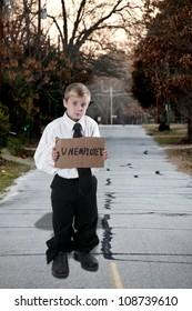 Handsome little boy holding up an unemployment sign