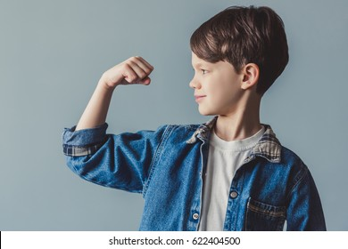 Handsome little boy in jean clothes is showing his muscles and smiling, on gray background