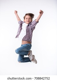 Handsome little boy is jumping, looking at camera and smiling, on light background
