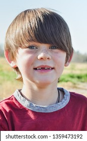 Handsome little boy missing teeth outdoors. Little boy with freckles missing teeth. Baby teeth falling out. Close up of a young male with missing teeth in Delcambre, Louisiana.