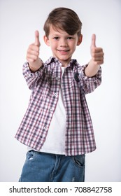 Handsome little boy is showing thumbs, looking at camera and smiling, on light background