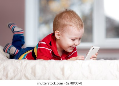 Handsome little boy with smartphone playing game on sofa at home