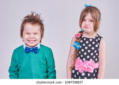 A handsome little boy, wearing a blue bow tie and a green sweater, laughs at a crying girl