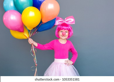 Handsome little clown holding a lot of balloons. Celebrate birthday