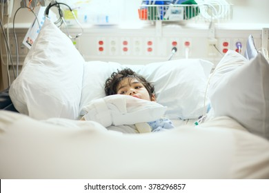 Handsome little disabled nine year old boy lying sick in hospital bed.  Child has cerebral palsy