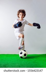 Handsome little football player with surprise facial expression. You talking to me. Little boy goalkeeper in white uniform pointing to himself with question if he did something wrong