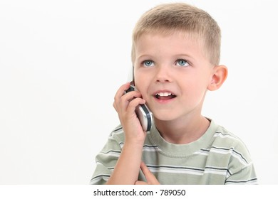 Handsome little four year old boy speaking on cellphone.  Shot in studio over white.