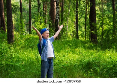 Handsome little happy smiling child (boy) walking and having fun in the green forest (park) and breathing fresh air