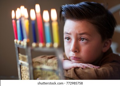 Handsome little Jewish boy with brown styled pompadour staring and meditating on Hanukkah candles in a  gold menorah during Hanukkah time of the festival of lights