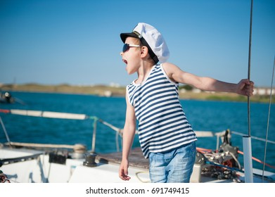 handsome little kid wearing sailor shirt and captain hat and sunglasses giving orders loudly shouting aboard