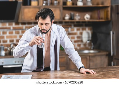 handsome loner businessman drinking water in morning at kitchen