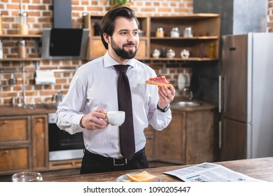 handsome loner businessman having breakfast at kitchen