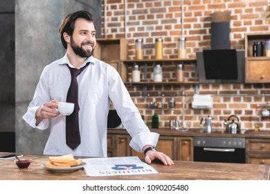 handsome loner businessman holding cup of coffee and looking away at kitchen