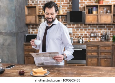 handsome loner businessman holding cup of coffee and reading newspaper at kitchen