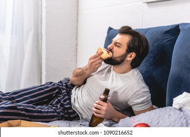 handsome loner eating pizza and holding bottle of beer in bedroom