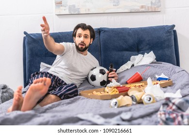 handsome loner gesturing while watching football game with beer in bedroom