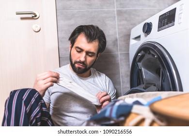 handsome loner holding dirty sock near washing machine in bathroom