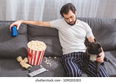 handsome loner sitting with bulldog on sofa and holding drink in living room