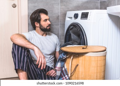 handsome loner sitting on floor and looking at washing machine in bathroom