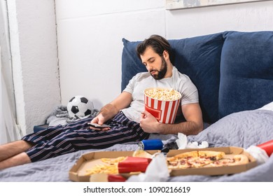 handsome loner sleeping with popcorn and remote control in bedroom