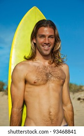 Handsome long haired blonde surfer standing in front of his surfboard.