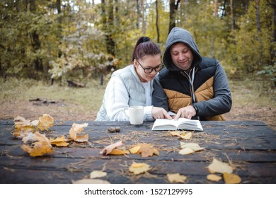 Handsome loving couple sitting on the bench in the autumn park reading a book, having fun together. Love and tenderness. Relationships, friendships, education, lifestyle concept