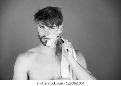 Handsome macho or bearded man with naked chest shaving beard with safety razor, white cream or foam and bathing towel on neck on green background. Beauty, skincare, hygiene, grooming, copy space