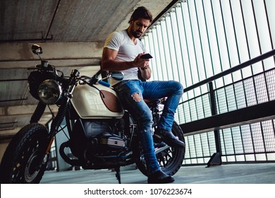 Handsome macho man with beard sitting on his motorcycle and looking at phone