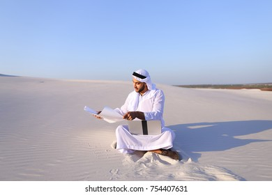 Handsome male Arab businessman and construction worker uses computer for design, busy developing complex schemes and opens drawing for checking and clarifying details sitting on white sand in
