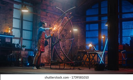 Handsome Male Artist Uses an Angle Grinder to Make Brutal Metal Sculpture in Studio. Hipster Guy Polishes Metal Tube with Sparks Flying Off It. Contemporary Fabricator Creating Abstract Steel Art.