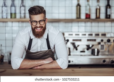Handsome male barista is working in coffee shop. Bearded man behind the bar counter is making coffee.