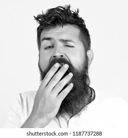 Handsome male with beard having sleepy boring look before the meeting he doesn't like.Tired or bored bearded hipster young man covering mouth while yawning, feeling exhausted after hard day at work.