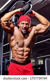 Schöner männlicher Bodybuilder im Fitnessraum. Grosser starker Mann während des Trainings im Fitnessraum. Sportler, Trainer oder Trainer mit großen Muskeln