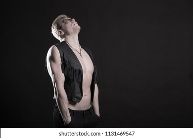 Handsome male bodybuilder in leather vest on a black background