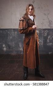 Handsome male in brown cloak, Steam punk style. Retro man portrait over grunge background.