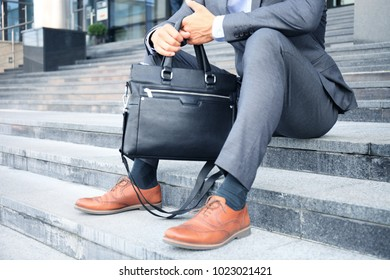 Handsome male business executive sitting on stairs outside a building.