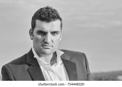 handsome male businessman with serious face in black jacket and white shirt outdoor on cloudy sky background